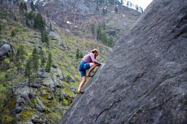 Developers love challenges: man climbing a mountain